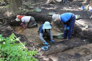 写真は、盛土範囲を解明するため、以前の調査地点を再び掘りかえす作業をしています。