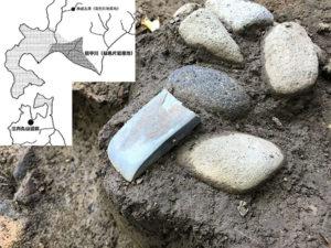 磨製石斧(写真中央の青緑色の石)が出土した状況です。